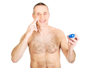 Portrait of a man applying cream on his face