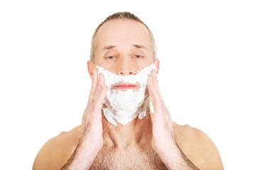 Portrait of a man applying shaving foam