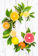Citrus fruits on white wood background.Vitamin c letter