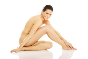 Nude woman sitting and touching her feet