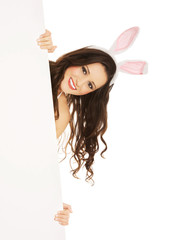 Woman wearing bunny ears and holding an empty baner