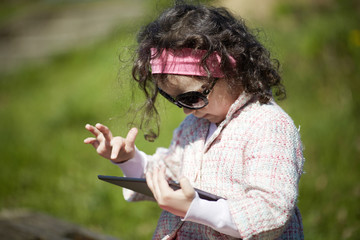 little girl uses tablet outdoors
