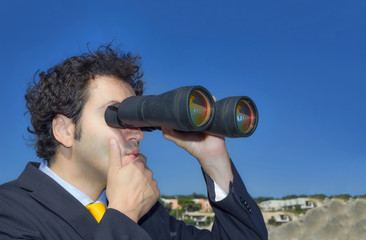 Business man  with binoculars looking at the sky