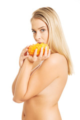 Beautiful nude woman holding kiwano