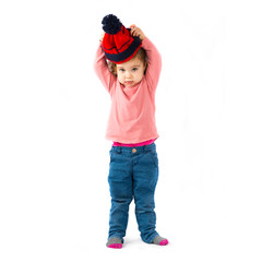 Little girl puttining on a Christmas hat over white background