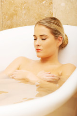 Beautiful woman relaxing in bathtub with her eyes closed