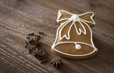 Gingerbread bell with spices on wooden background