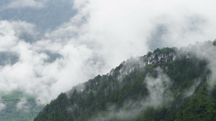 Fog rolls across flowing over Mountains