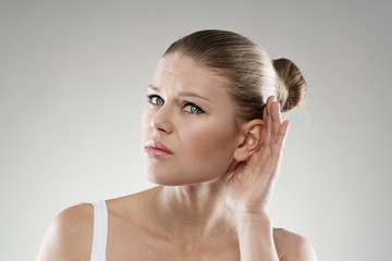 Deafness. Young woman having hearing problems