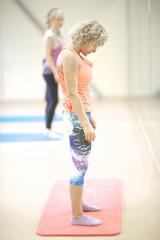 Woman in sportwear warming up in the gym, bending head