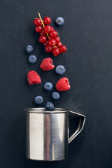 metal cup and berries on a black background