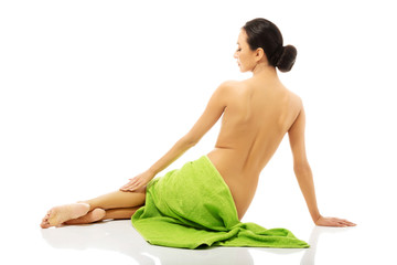 Back view of woman lying wrapped in towel
