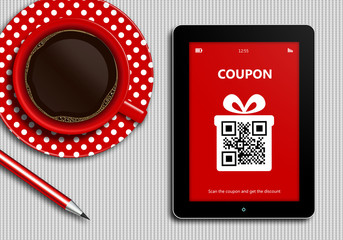 tablet with discount coupon and  cup of coffee lying on tableclo