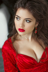 Brunette gorgeous young woman with red lips wearing in red dress