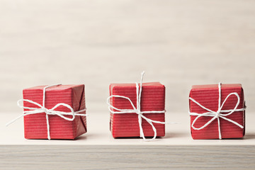 Three red gift boxes on wooden background