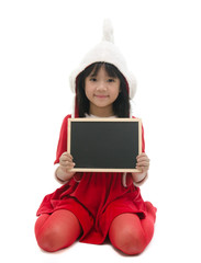 Asian girl in santa costume sitting and holding chalkboard