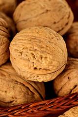 Whole walnuts and walnut kernel in a wicker basket