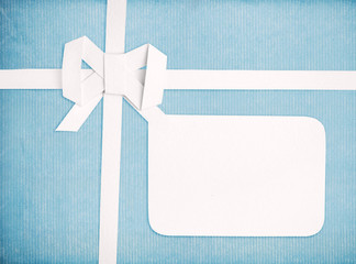 Gift ribbon and bow with blank gift tag, blue retro background