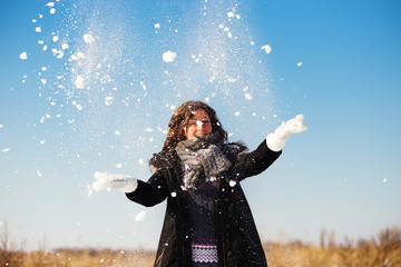 Happy young woman have fun and enjoy fresh snow at beautiful win