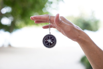 Hand holding the compass.