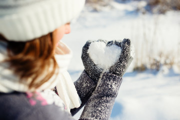 Young women holding heart shaped snow in hands
