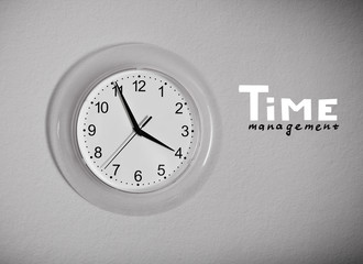 "Clock on the wall with ""Time management"" lettering, black and wh"