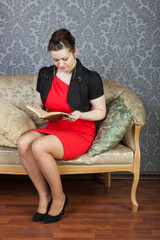 young sexy woman sits on a sofa and a reads green book