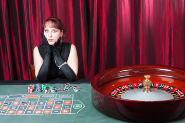 sexy girl wearing black dress and gloves plays in a casino
