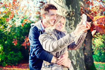 smiling couple taking selfie in autumn