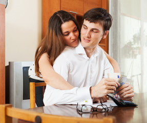 Young couple with money and financial documents