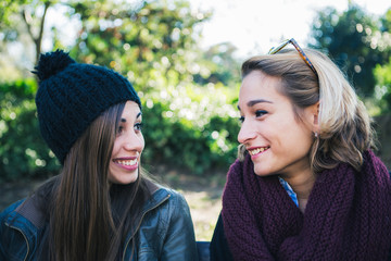 Two young woman sitting in the park and talking about something,