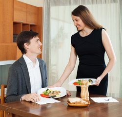 Loving woman serving dinner to beloved man