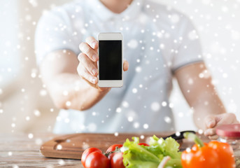 close up of man showing smartphone in kitchen