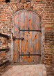 Old wooden door in brick wall of castle