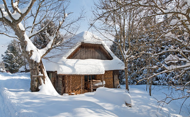Wooden building under snow with firewood storage, sunny winter