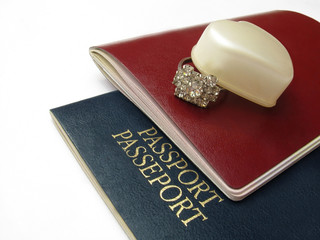 blue passport and red passport with proposal ring