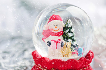 A snow globe with snowman on festive background
