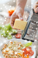 close up of male hands with grater grating cheese