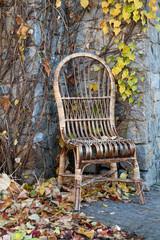 Old wicker chair near stony wall in yellow fallen leafs