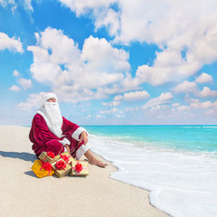 Santa Claus with many christmas golden gifts relaxing on tropica