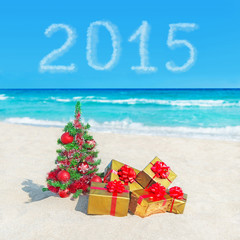 Christmas tree and golden gifts at sea beach. Concept for New Ye