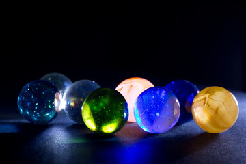 Shiny Colorful Translucent Glass Balls Against Black Background