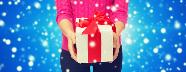 close up of woman in pink sweater holding gift box