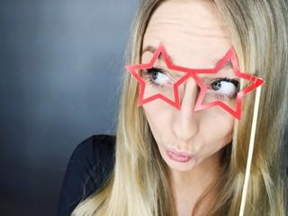 Frau blickt durch Brille aus Pappe