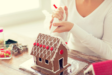 close up of woman making gingerbread house at home
