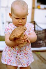 One year old baby girl  with mushroom boletus