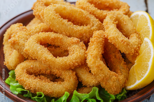 Fotobehang Schaaldieren fried squid rings breaded with lemon