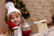 Girl in knitted hat and gloves holding Christmas ball