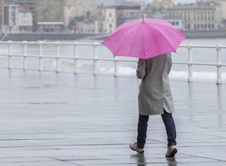 Mujer con paraguas paseando por la ciudad