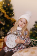 Girl in knitted hat with clock over Christmas tree